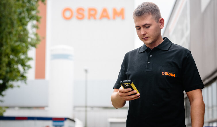 Digitalization in manufacturing: A Osram worker looking at his ticket manager.
